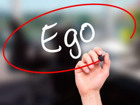 pretentious: Man Hand writing Ego with black marker on visual screen. Isolated on background. Business, technology, internet concept. Stock Photo
