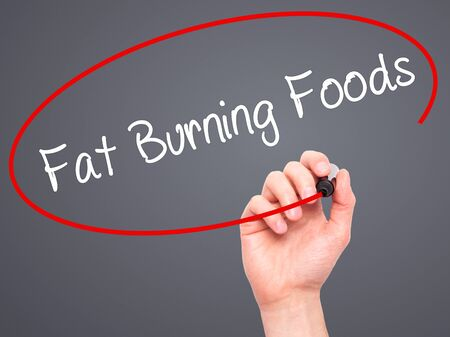 fat burning: Man Hand writing Fat Burning Foods with black marker on visual screen. Isolated on grey. Business, technology, internet concept. Stock Photo