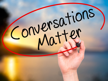business matter: Man Hand writing Conversations Matter with black marker on visual screen. Isolated on nature. Business, technology, internet concept. Stock Image
