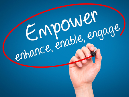 enable: Man Hand writing Empower enhance, enable, engage with black marker on visual screen. Isolated on blue. Business, technology, internet concept. Stock Photo