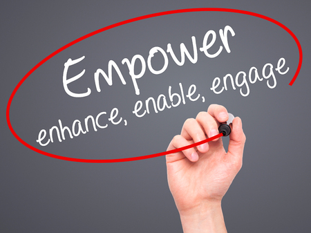 enhance: Man Hand writing Empower enhance, enable, engage with black marker on visual screen. Isolated on grey. Business, technology, internet concept. Stock Photo