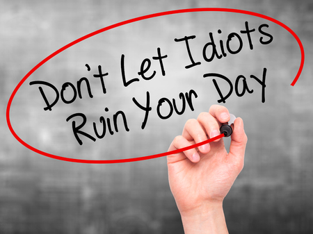 irrelevant: Man Hand writing Dont Let Idiots Ruin Your Day with black marker on visual screen. Isolated on grey. Business, technology, internet concept. Stock Photo Stock Photo