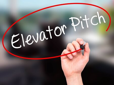 business pitch: Man Hand writing Elevator Pitch with black marker on visual screen. Isolated on office. Business, technology, internet concept. Stock Photo