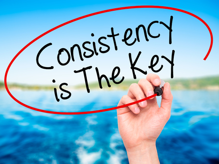 consistency: Man Hand writing Consistency is The Key with black marker on visual screen. Isolated on nature. Business, technology, internet concept. Stock Photo Stock Photo