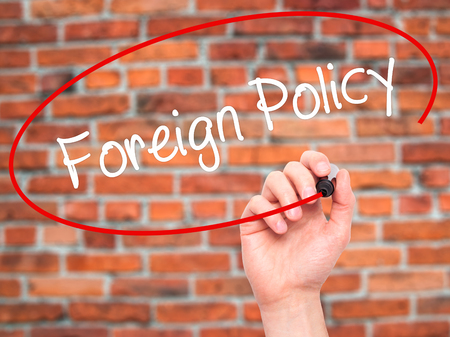foreign nation: Man Hand writing Foreign Policy with black marker on visual screen. Isolated on background. Business, technology, internet concept. Stock Photo Stock Photo