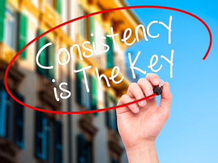 consistency: Man Hand writing Consistency is The Key with black marker on visual screen. Isolated on city. Business, technology, internet concept. Stock Photo