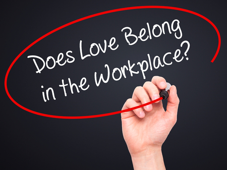 belong: Man Hand writing Does Love Belong in the Workplace? with black marker on visual screen. Isolated on black. Business, technology, internet concept. Stock Photo