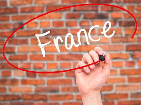 champagne region: Man Hand writing France with black marker on visual screen. Isolated on bricks. Business, technology, internet concept. Stock Photo Stock Photo