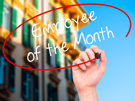 recognizing: Man Hand writing Employee of the Month  with black marker on visual screen. Isolated on city. Business, technology, internet concept. Stock Photo