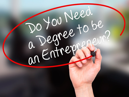 business degree: Man Hand writing Do You Need a Degree to be an Entrepreneur? with black marker on visual screen. Isolated on office. Business, technology, internet concept. Stock Photo