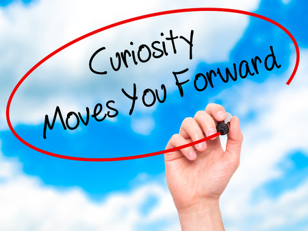 street wise: Man Hand writing Curiosity Moves You Forward with black marker on visual screen. Isolated on background. Business, technology, internet concept. Stock Photo Stock Photo