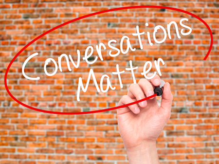 business matter: Man Hand writing Conversations Matter with black marker on visual screen. Isolated on bricks. Business, technology, internet concept. Stock Image