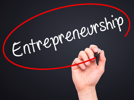 self starter: Man Hand writing Entrepreneurship with black marker on visual screen. Isolated on black. Business, technology, internet concept. Stock Image
