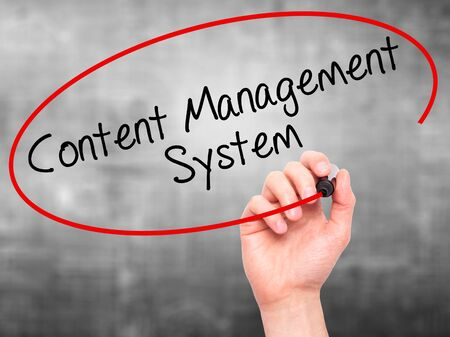 ecm: Man Hand writing Content Management System  with black marker on visual screen. Isolated on grey. Business, technology, internet concept. Stock Photo