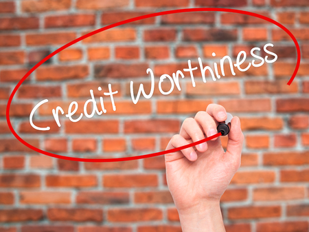 creditworthiness: Man Hand writing Credit Worthiness with black marker on visual screen. Isolated on bricks. Business, technology, internet concept. Stock Photo