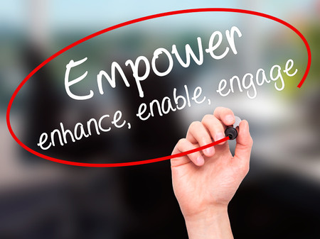 enable: Man Hand writing Empower enhance, enable, engage with black marker on visual screen. Isolated on office. Business, technology, internet concept. Stock Photo Stock Photo