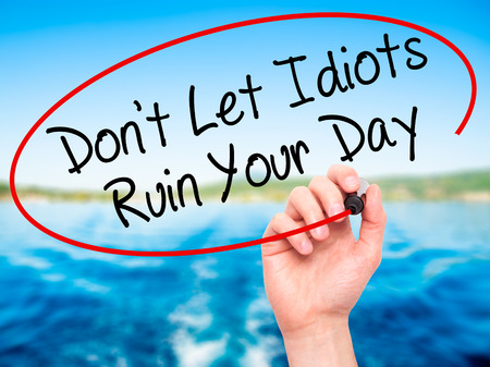 stupidity: Man Hand writing Dont Let Idiots Ruin Your Day with black marker on visual screen. Isolated on nature. Business, technology, internet concept. Stock Photo