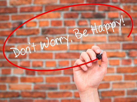 dont worry: Man Hand writing Dont Worry, Be Happy! with black marker on visual screen. Isolated on bricsk. Business, technology, internet concept.
