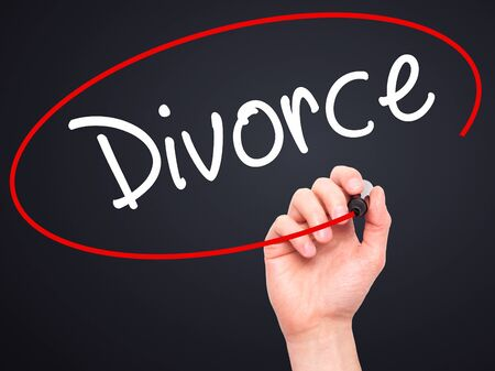 ex wife: Man Hand writing Divorce  with black marker on visual screen. Isolated on black. Business, technology, internet concept. Stock Photo Stock Photo