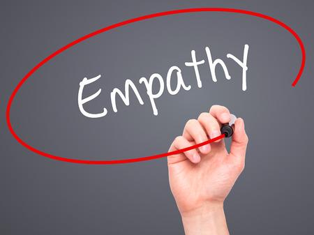 empatia: Hombre de la mano escribiendo Empat�a con marcador negro en la pantalla visual. Aislado en gris. Negocios, la tecnolog�a, el concepto de internet. Foto de stock