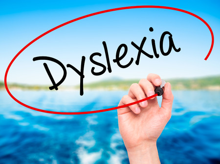 dyslexic: Man Hand writing Dyslexia with black marker on visual screen. Isolated on background. Business, technology, internet concept. Stock Photo