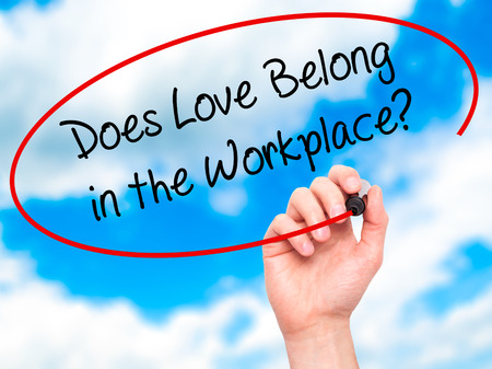 belong: Man Hand writing Does Love Belong in the Workplace? with black marker on visual screen. Isolated on sky. Business, technology, internet concept. Stock Photo
