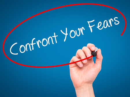 unafraid: Man Hand writing Confront Your Fears with black marker on visual screen. Isolated on background. Business, technology, internet concept. Stock Photo