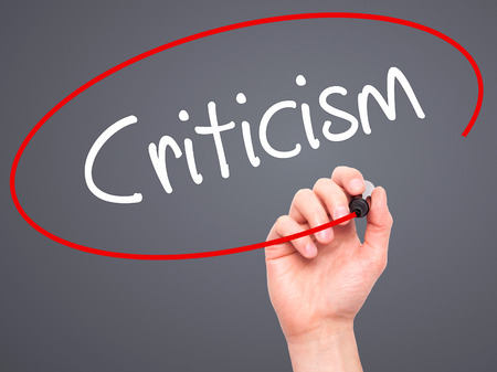 criticism: Man Hand writing Criticism with black marker on visual screen. Isolated on background. Business, technology, internet concept. Stock Photo