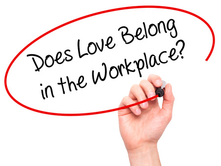 belong: Man Hand writing Does Love Belong in the Workplace? with black marker on visual screen. Isolated on white. Business, technology, internet concept. Stock Photo