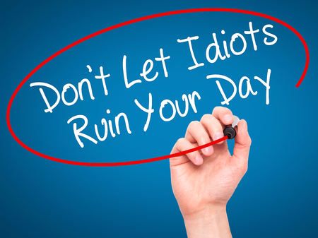 naivety: Man Hand writing Dont Let Idiots Ruin Your Day with black marker on visual screen. Isolated on blue. Business, technology, internet concept. Stock Photo Stock Photo