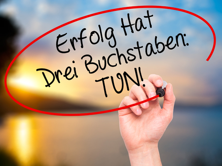 buchstaben: Man Hand writing Erfolg Hat Drei Buchstaben: Tun! (Success Has Three Letters: Do in German) with black marker on visual screen. Isolated on background. Business,  internet concept. Stock Photo Stock Photo