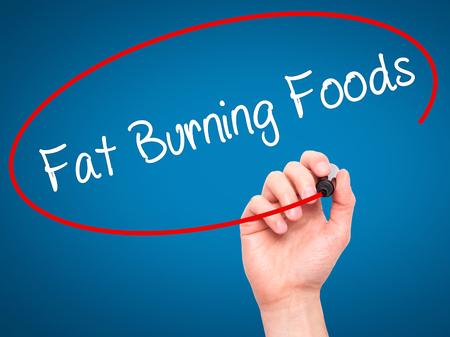 fat burning: Man Hand writing Fat Burning Foods with black marker on visual screen. Isolated on blue. Business, technology, internet concept. Stock Photo