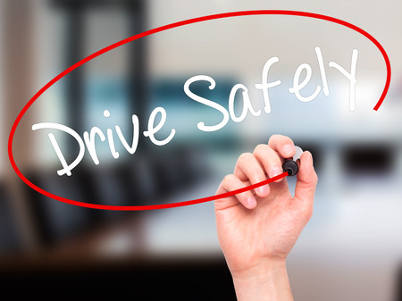 drive safely: Man Hand writing  Drive Safely with black marker on visual screen. Isolated on office. Business, technology, internet concept. Stock Photo Stock Photo