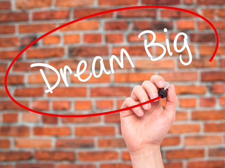street wise: Man Hand writing Dream Big  with black marker on visual screen. Isolated on bricks. Business, technology, internet concept. Stock Photo
