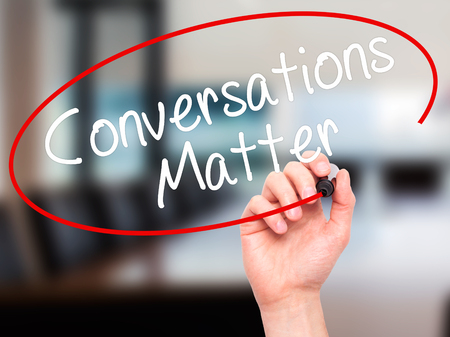 business matter: Man Hand writing Conversations Matter with black marker on visual screen. Isolated on office. Business, technology, internet concept. Stock Image Stock Photo