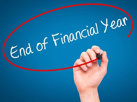 jurisdictions: Man Hand writing End of Financial Year with black marker on visual screen. Isolated on background. Business, technology, internet concept. Stock Photo Stock Photo