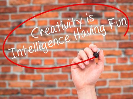 Man Hand Writing La créativité est de l'intelligence S'amuser avec un marqueur noir sur l'écran visuel. Isolé sur des briques. Affaires, technologie, concept internet. Photo