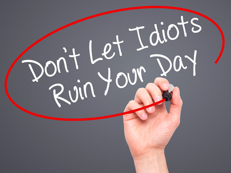 stupidity: Man Hand writing Dont Let Idiots Ruin Your Day with black marker on visual screen. Isolated on grey. Business, technology, internet concept. Stock Photo Stock Photo