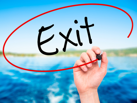 withdrawing: Man Hand writing Exit with black marker on visual screen. Isolated on background. Business, technology, internet concept. Stock Photo