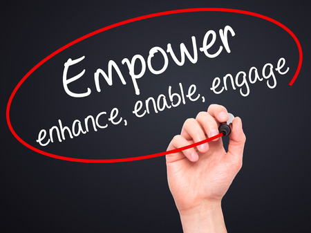 enable: Man Hand writing Empower enhance, enable, engage with black marker on visual screen. Isolated on black. Business, technology, internet concept. Stock Photo