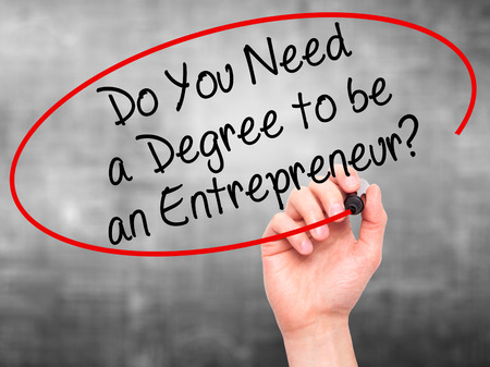 business degree: Man Hand writing Do You Need a Degree to be an Entrepreneur? with black marker on visual screen. Isolated on grey. Business, technology, internet concept. Stock Photo