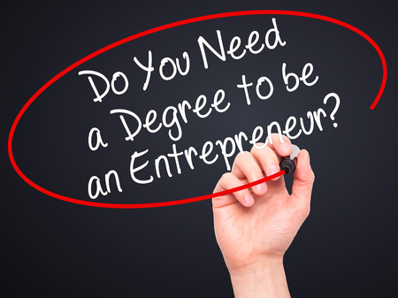 business degree: Man Hand writing Do You Need a Degree to be an Entrepreneur? with black marker on visual screen. Isolated on black. Business, technology, internet concept. Stock Photo