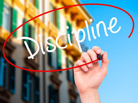 disciplined: Man Hand writing Discipline with black marker on visual screen. Isolated on city. Business, technology, internet concept. Stock Photo Stock Photo