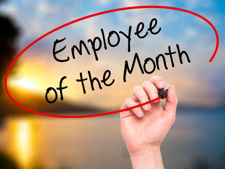 Man Hand writing Employee of the Month  with black marker on visual screen. Isolated on nature. Business, technology, internet concept. Stock Photo