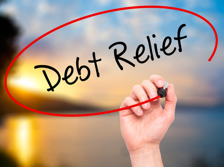 writing on screen: Man Hand writing Debt Relief with black marker on visual screen. Isolated on nature. Business, technology, internet concept. Stock Photo