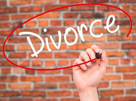 ex wife: Man Hand writing Divorce  with black marker on visual screen. Isolated on bricks. Business, technology, internet concept. Stock Photo