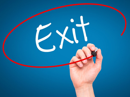 downsize: Man Hand writing Exit with black marker on visual screen. Isolated on background. Business, technology, internet concept. Stock Photo