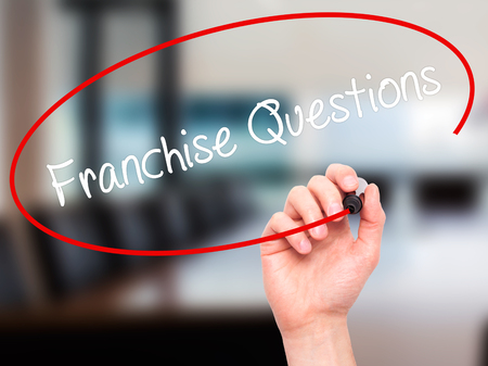restaurant questions: Man Hand writing Franchise Questions with black marker on visual screen. Isolated on office. Business, technology, internet concept. Stock Photo