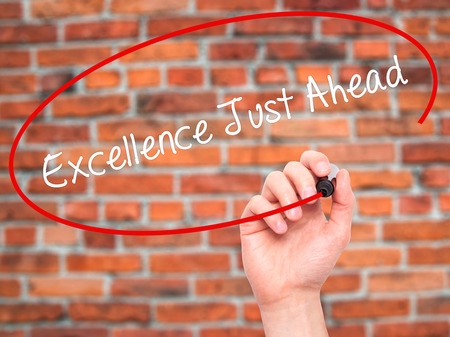 satisfactory: Man Hand writing Excellence Just Ahead with black marker on visual screen. Isolated on bricks. Business, technology, internet concept. Stock Photo