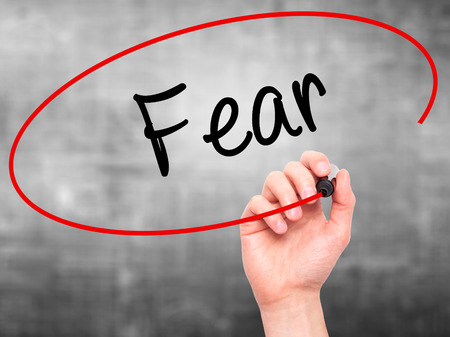 unafraid: Man Hand writing Fear with black marker on visual screen. Isolated on grey. Business, technology, internet concept. Stock Photo